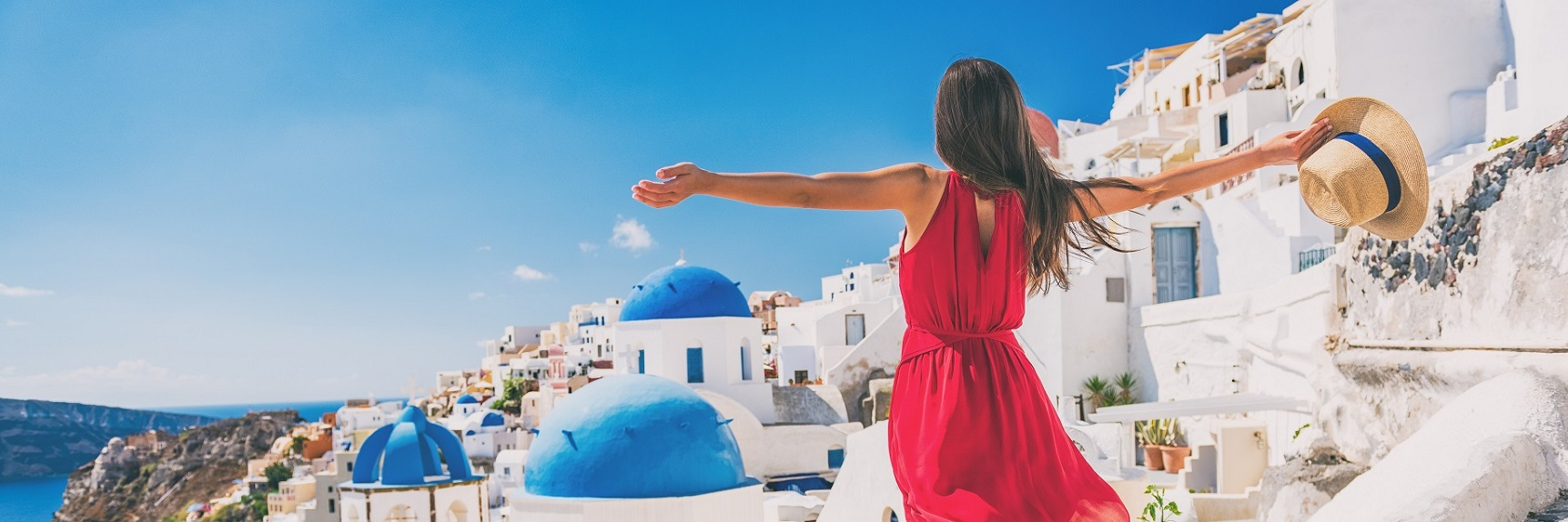 Europe travel vacation fun summer woman feeling free dancing with arms open in freedom at Oia, Santorini, Greece island. Carefree girl tourist banner panorama.