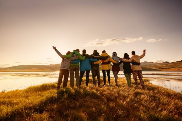 Big happy family is standing and hugging together against lake in mountains and sunset sky